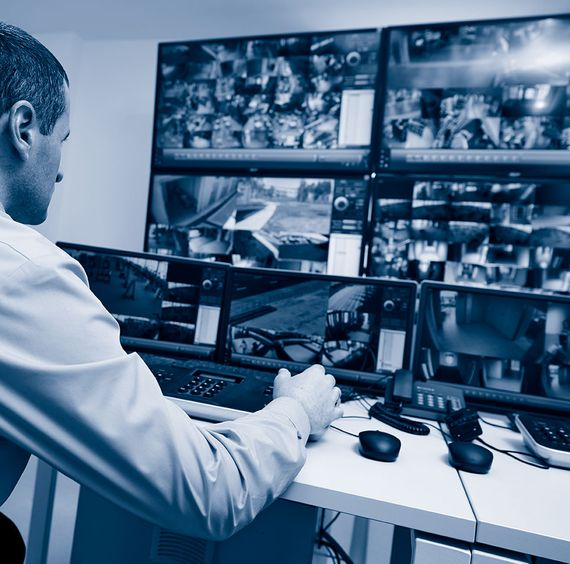 Man watching TV monitors of CCTV footage